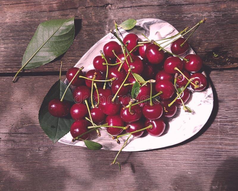 Frutta rossa fresca della ciliegia in piatto sul fondo di legno della tavola fotografia stock libera da diritti