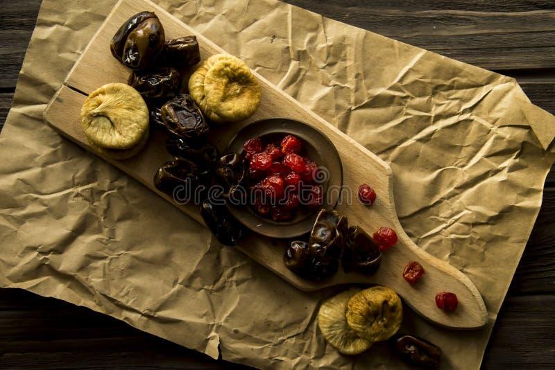 Frutta secca sulla plancia della cucina - datteri, fichi e ciliege secche fotografia stock
