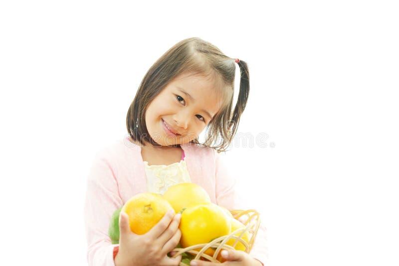 Frutta sorridente della tenuta della ragazza fotografia stock