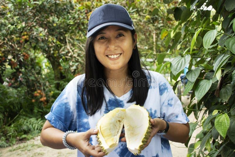 Frutta tailandese della tenuta della donna del viaggiatore e del durian di manifestazione nel festival del buffet di frutti immagini stock libere da diritti