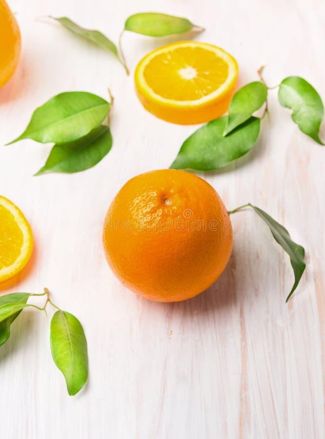 Frutti arancio crudi con le foglie verdi e la fetta fotografia stock