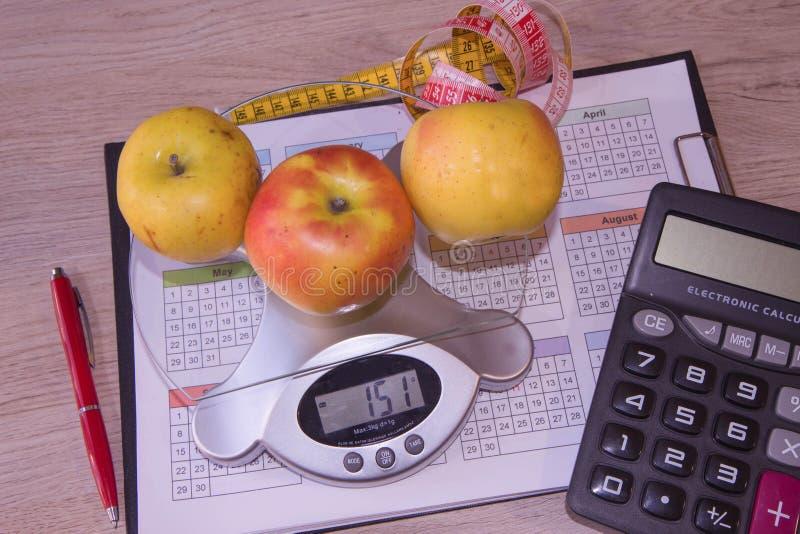 Frutti, Bilancia, calcolatore e centimetro su un fondo bianco Stia il concetto a dieta fotografie stock