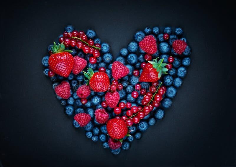 Frutti del preparato della bacca nella forma del cuore su fondo nero Bacche ordinate - fragola, lampone, ribes, mirtillo e fotografie stock libere da diritti