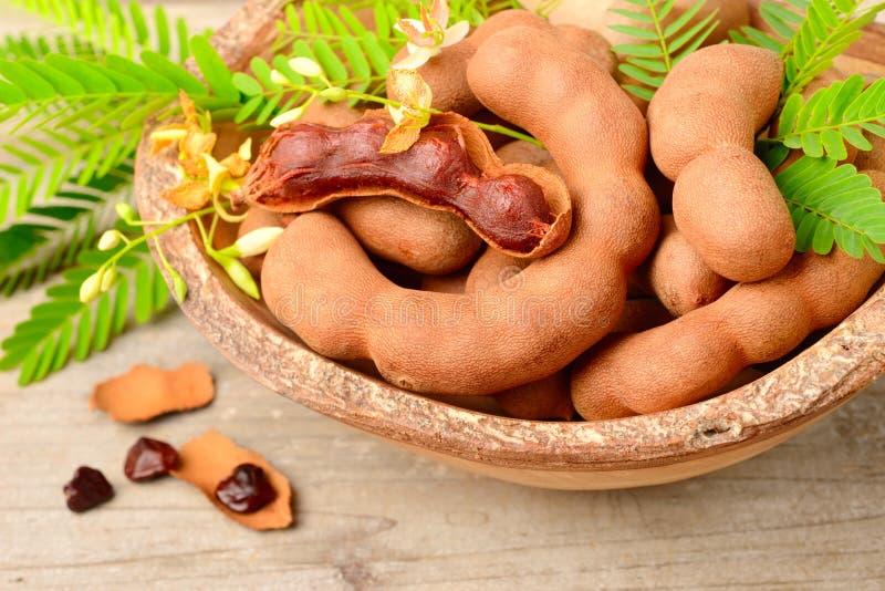 Frutti del tamarindo e foglie fresche sul bordo di legno immagine stock libera da diritti