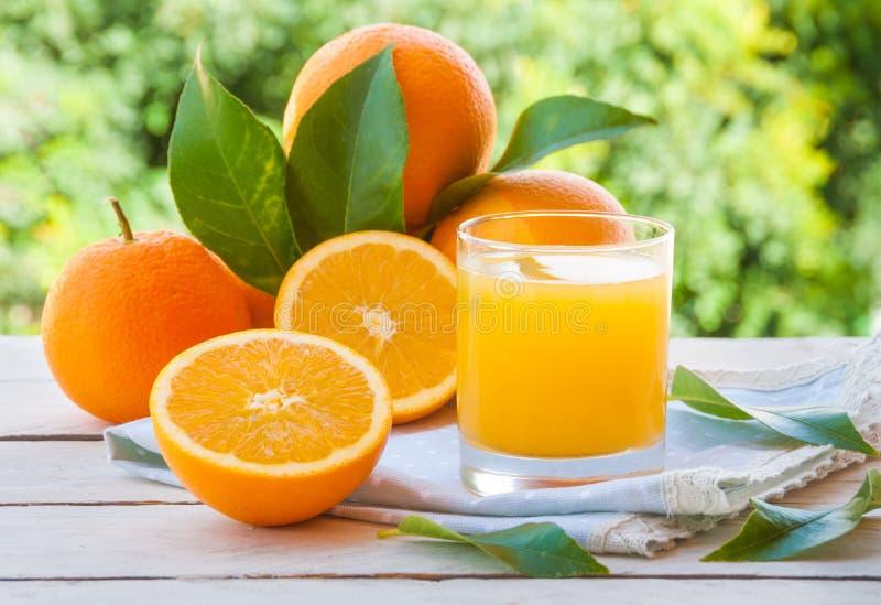 Frutti delle arance e del succo d'arancia fresco con le foglie all'aperto fotografia stock
