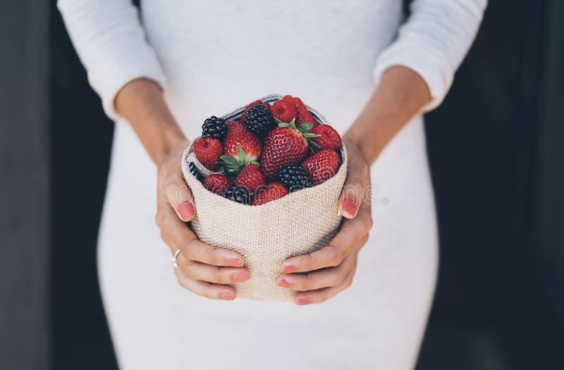Frutti di bacche sani e succosi in mani della donna con il vestito bianco immagini stock libere da diritti