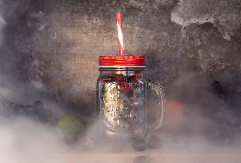 Frutti di forma del barattolo del frullato Uva, lampone, calce, fondo scuro fotografia stock libera da diritti