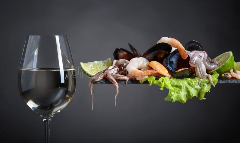 Frutti di mare deliziosi crudi misti con le fette della calce e vetro di vino bianco fotografie stock libere da diritti