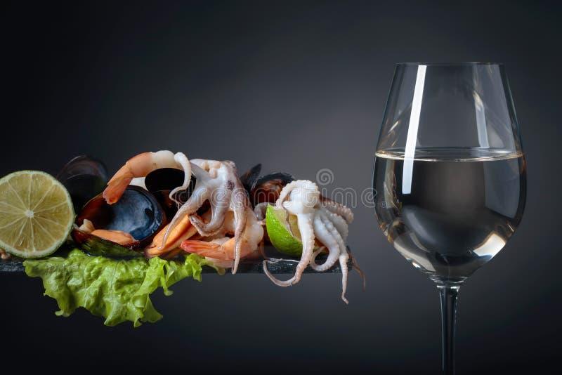 Frutti di mare deliziosi crudi misti con le fette della calce e vetro di vino bianco immagini stock libere da diritti