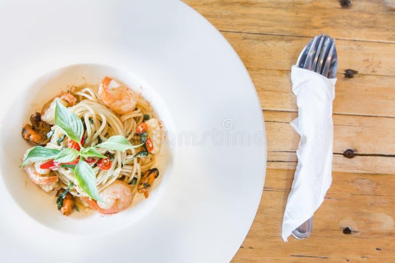 Frutti di mare piccanti degli spaghetti in piatto bianco immagine stock