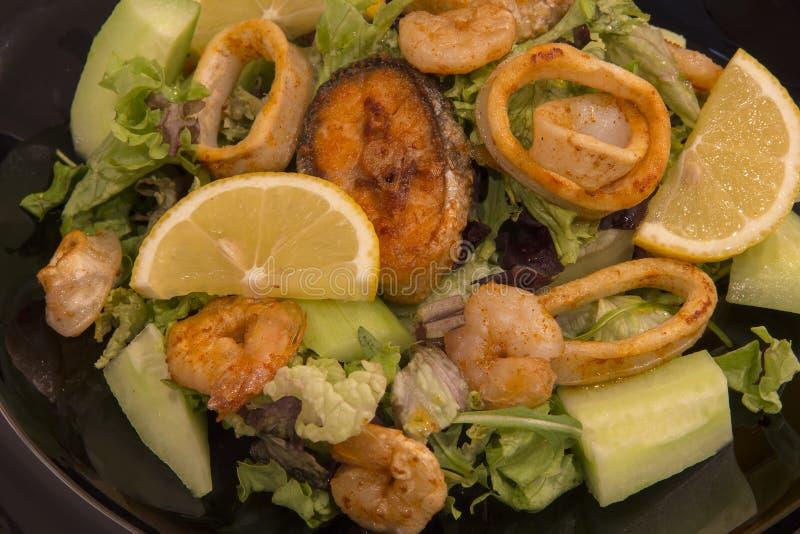 Frutti di mare saporiti gamberetti, pesce e calamari dell'insalata mista con il limone e le verdure fotografia stock libera da diritti