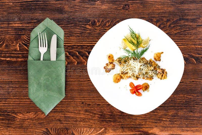 Frutti di mare su un piatto con gli apparecchi su una tavola di legno, su un piatto per il menu e sulla pubblicità immagini stock