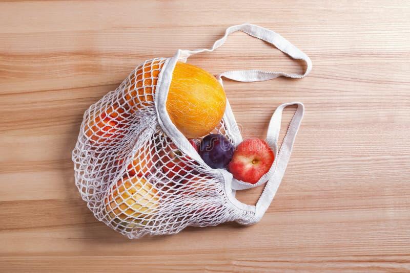 Frutti differenti di estate in sacchetto della spesa riutilizzabile sulla tavola di legno fotografie stock libere da diritti
