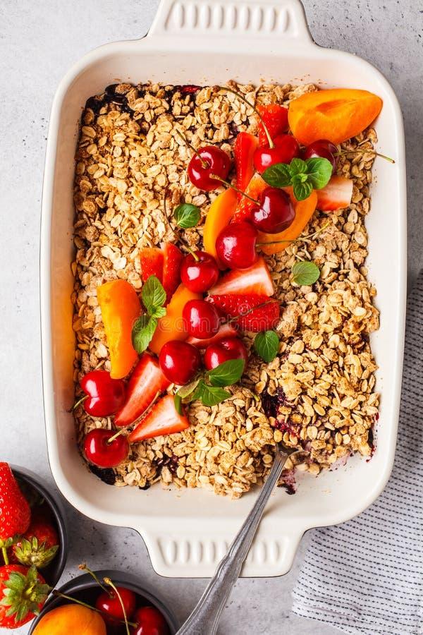 Frutti e briciola dell'avena delle bacche nel piatto del forno su fondo grigio, vista superiore fotografia stock libera da diritti