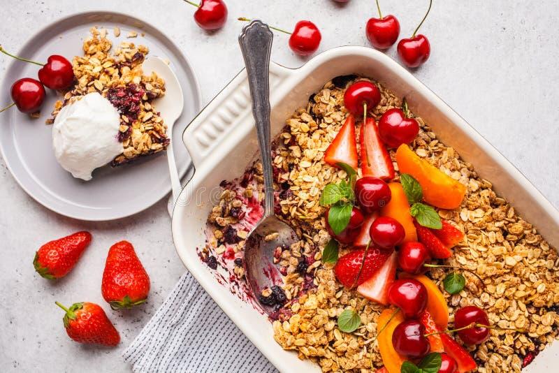 Frutti e briciola dell'avena delle bacche nel piatto del forno su fondo grigio, vista superiore fotografia stock
