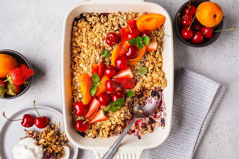 Frutti e briciola dell'avena delle bacche nel piatto del forno su fondo grigio, vista superiore immagine stock