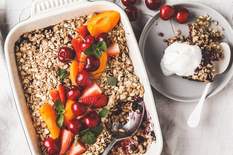 Frutti e briciola dell'avena delle bacche nel piatto del forno su fondo grigio, vista superiore fotografie stock