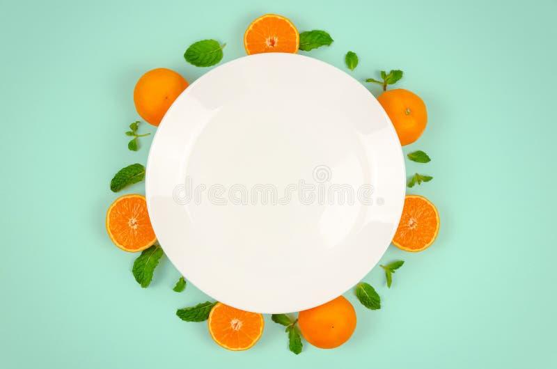 Frutti e foglie di menta arancio freschi sulla vista superiore con il piatto bianco e sul fondo pastello di colore verde per il c fotografie stock libere da diritti