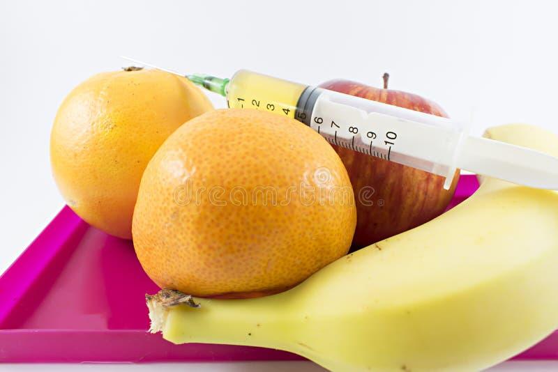 Frutti e siringa su fotografia stock