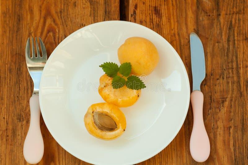Frutti freschi maturi dell'albicocca su un piatto bianco sui precedenti di legno Spazio della copia, alimento sano delisious immagini stock libere da diritti