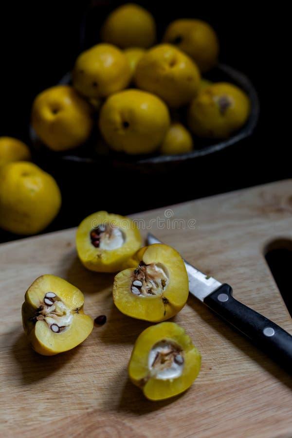 Frutti gialli strappati dei chaenomeles della cotogna su fondo scuro immagine stock