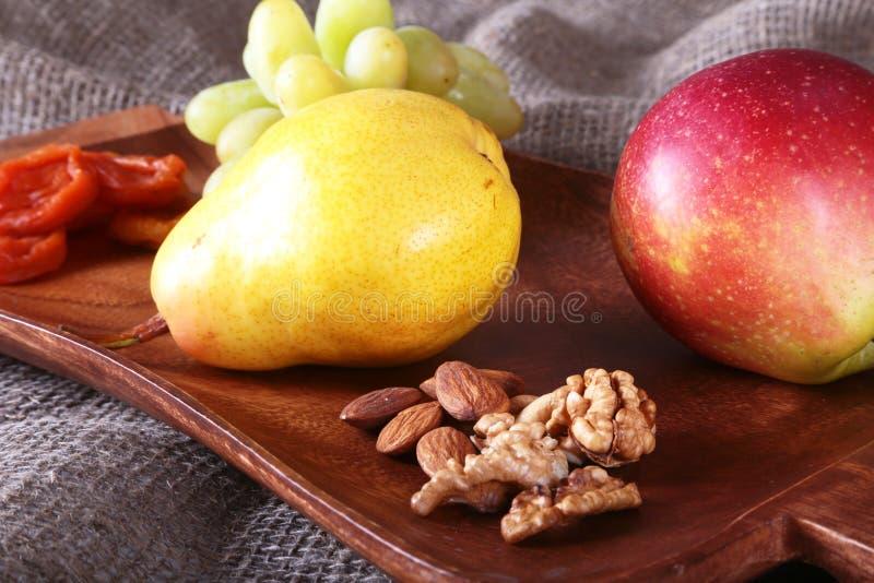 Frutti organici freschi sul vassoio di legno del servizio La mela assortita, la pera, uva, ha asciugato i frutti ed i dadi fotografie stock