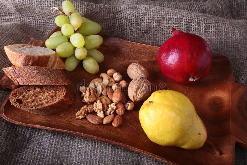 Frutti organici freschi sul vassoio di legno del servizio La mela assortita, la pera, uva, ha asciugato i frutti ed i dadi immagini stock libere da diritti