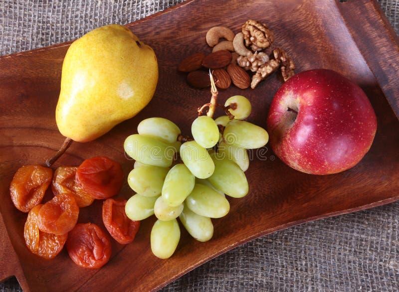 Frutti organici freschi sul vassoio di legno del servizio La mela assortita, la pera, uva, ha asciugato i frutti ed i dadi immagine stock