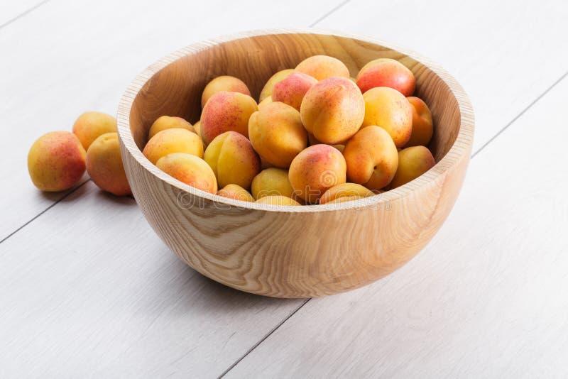 frutti organici maturi delle albicocche in ciotola di legno dell'albero di cenere su un fondo di legno bianco fotografie stock libere da diritti