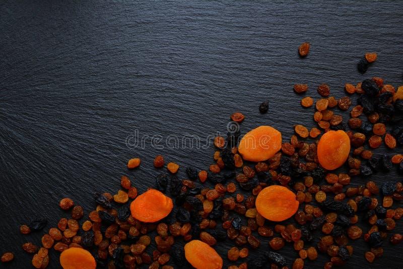 Frutti secchi: l'uva passa e le albicocche secche sull'ardesia nera imbarcano, p fotografia stock
