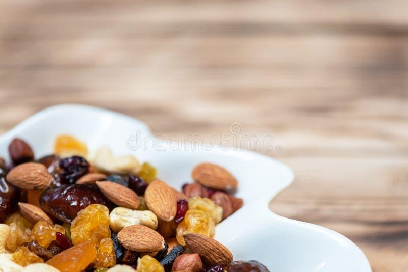 Frutti secchi in piatto bianco sulla tavola di legno, spazio della copia per testo Miscela delle varietà differenti di dadi e di  fotografia stock libera da diritti