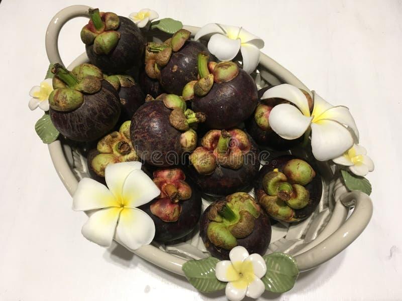 Frutti tropicali del mangostano in canestro ceramico, decorato con i fiori del frangipane fotografie stock libere da diritti