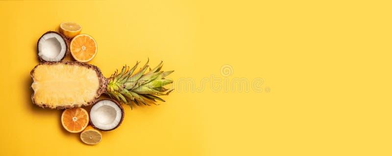 Frutti tropicali di estate con l'arancia, limone, ananas su un fondo giallo pastello fotografia stock