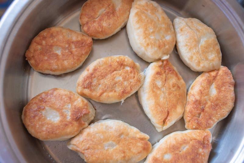 Fry délicieux tartes luxueuses faites maison avec une variété de garnitures dans de l'huile de légumes chaude sur une poêle blanc photos libres de droits