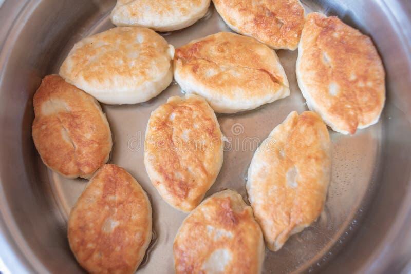 Fry délicieux tartes luxueuses faites maison avec une variété de garnitures dans de l'huile de légumes chaude sur une poêle blanc images libres de droits