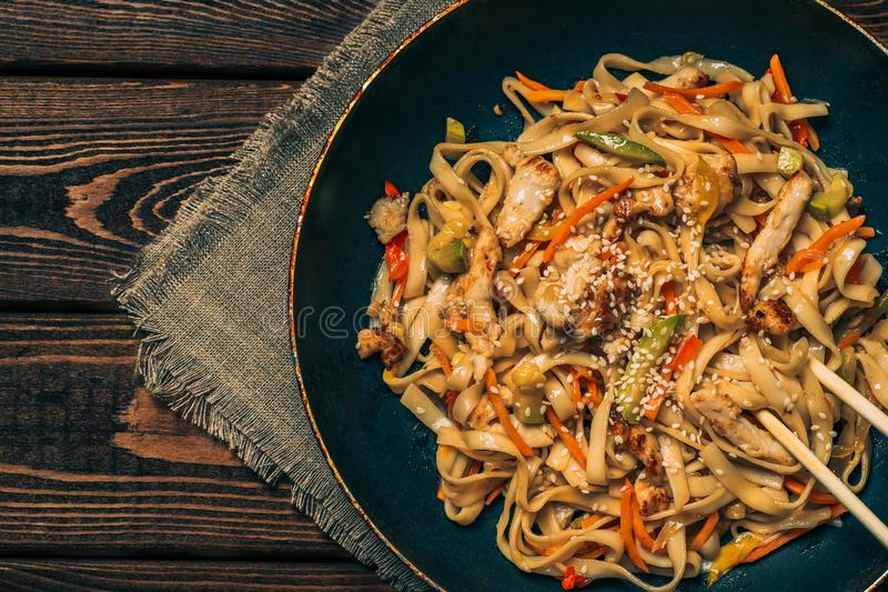 Fry noodles - traditional Chinese WOK with fried chicken and vegetables on wooden table, top view stock photography