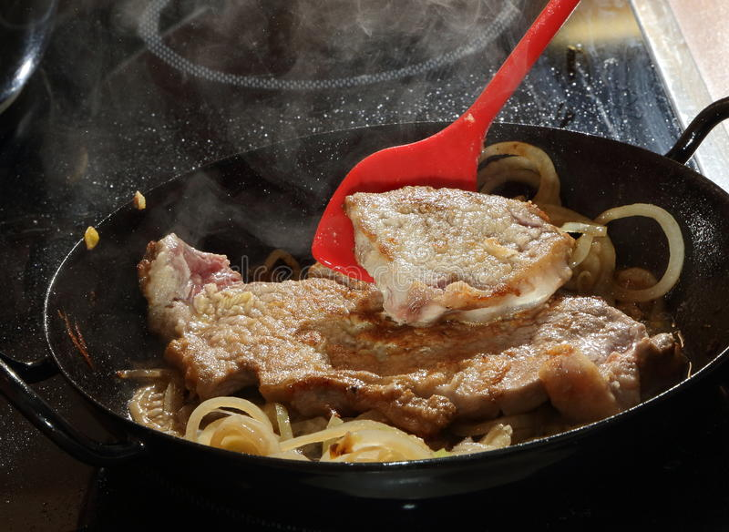 Frying beef with onions. Beef steaks coated with flour being fried in a hot metal pan with onions and red spatula royalty free stock photo