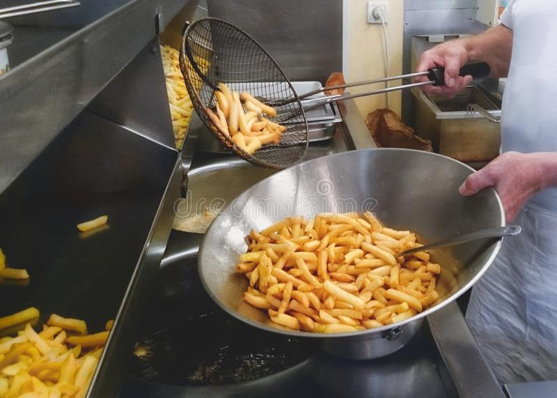 Frying French fries, Chips, Frites with double fry technique. stock photography