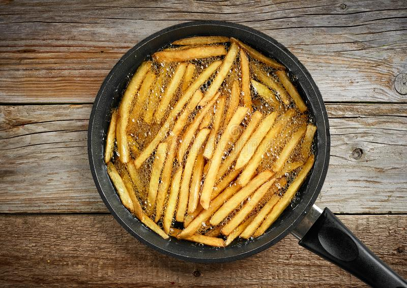 Frying french fries. In a pan with oil, top view stock image