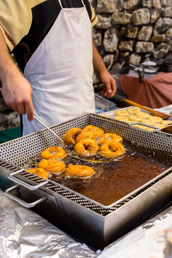 Frying homemade and delicious donuts on fresh olive oil. Typical spanish donuts royalty free stock photography