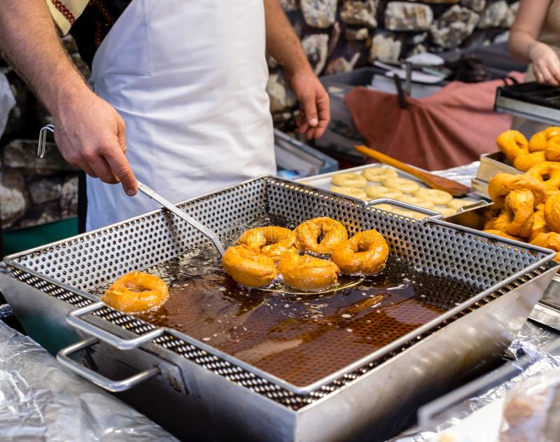 Frying homemade and delicious donuts on fresh olive oil. Typical spanish donuts. royalty free stock photo