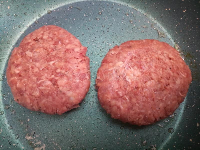Two raw thick organic beef burgers cooking royalty free stock image