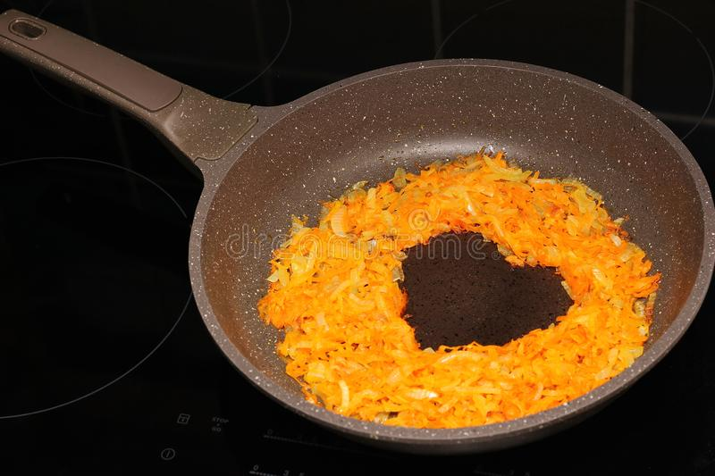 Frying pan on black induction cooker, heart shape of roasted carrot and onion on it royalty free stock photography