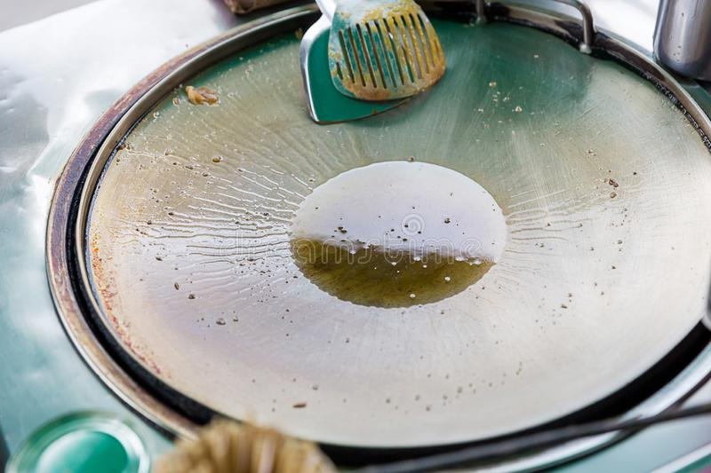 Frying pan with boiling oil on the stove. a cooking pan on a hot plate for making roti thailand street food market.  stock photography