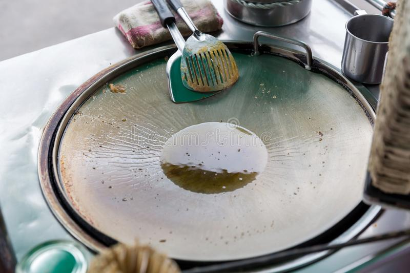 Frying pan with boiling oil on the stove. a cooking pan on a hot plate for making roti thailand street food market.  royalty free stock image