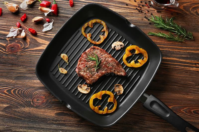 Frying pan with delicious grilled steak and vegetables on wooden table stock images