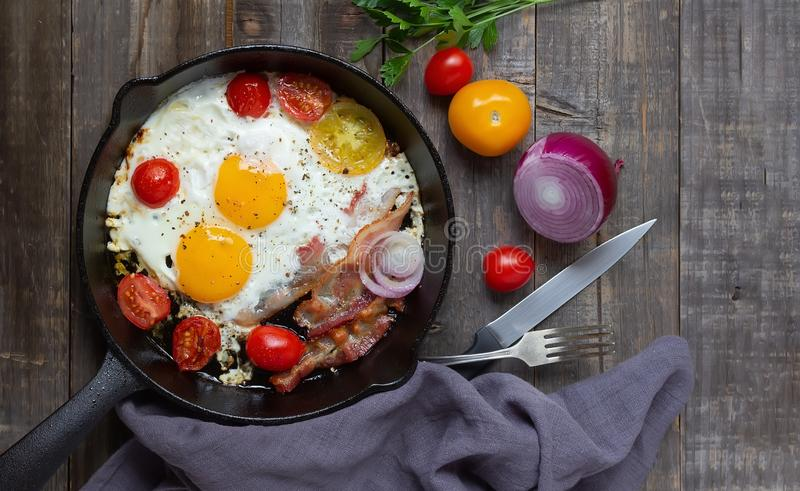 Frying pan with eggs, bacon and tomatoes. Top view, flat lay stock images