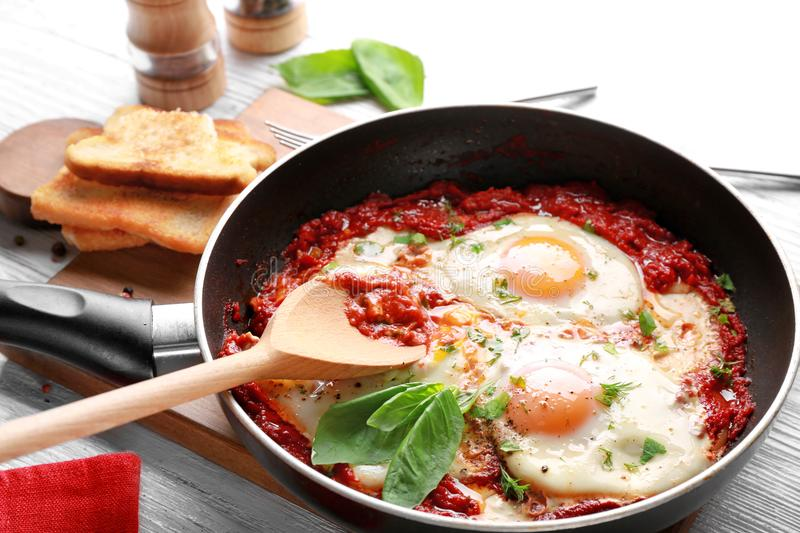 Frying pan with eggs in purgatory stock photos