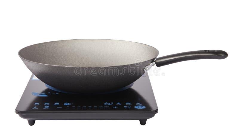 Frying pan on electric stove. Frying pan,iron cooking pan on induction cooker electric stove royalty free stock image