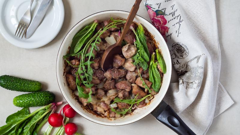 Frying pan of fried meat with greens and onions. Goulash. Near fresh cucumbers, radishes and spinach royalty free stock photos